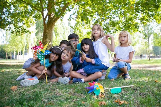 Aufgeregte kinder, die zusammen auf gras im park sitzen, wegschauen, windrad halten, leistung beobachten. kinderparty oder unterhaltungskonzept