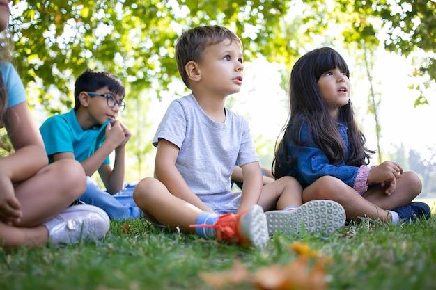 Aufgeregte kinder sitzen auf gras im park und schauen zusammen weg, sehen performance oder animatoren zeigen. kinderparty oder freundschaftskonzept