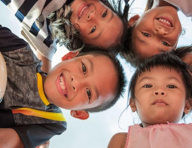 Aufgeregte kinder stehen im kreis, der kamera am zusammen spielen betrachtend umarmt