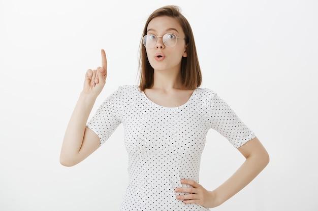 Aufgeregte kluge frau in gläsern schlagen plan vor, haben idee, heben zeigefinger nach oben