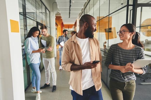 Aufgeregte kollegen, die zum arbeitsplatz gehen und geschichten austauschen