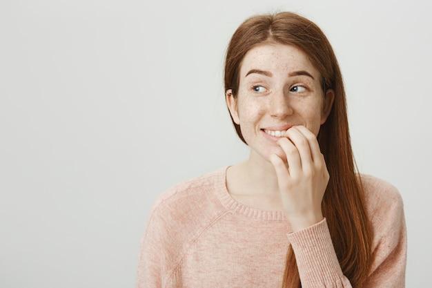 Aufgeregte lächelnde rothaarige weibliche berührungslippe und blick mit versuchung nach links