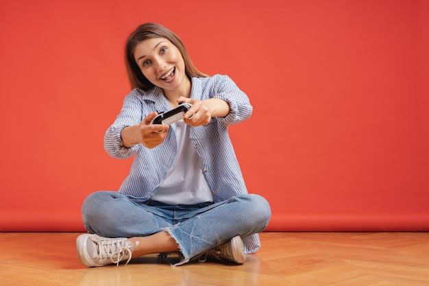 Aufgeregte lässige junge frau, die videospiele spielt, die spaß auf rot haben