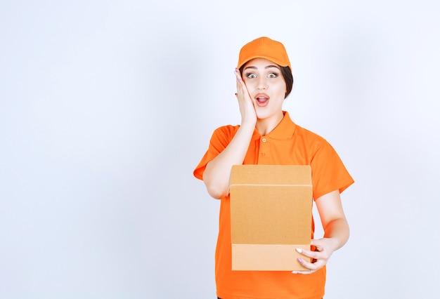 Aufgeregte lieferfrau, die unverpacktes paket in der weißen wand durchbohrt