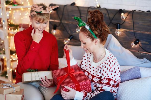 Aufgeregte mädchen, die weihnachtsgeschenk im bett öffnen