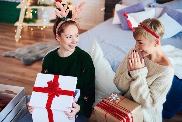 Aufgeregte mädchen, die weihnachtsgeschenk öffnen