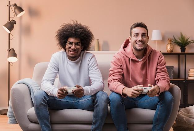 Aufgeregte männliche spielende freunde zu hause