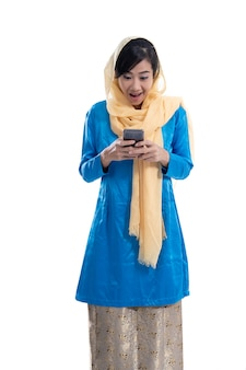 Aufgeregte muslimische frau, die ihr telefon lokalisiert über weißem hintergrund betrachtet