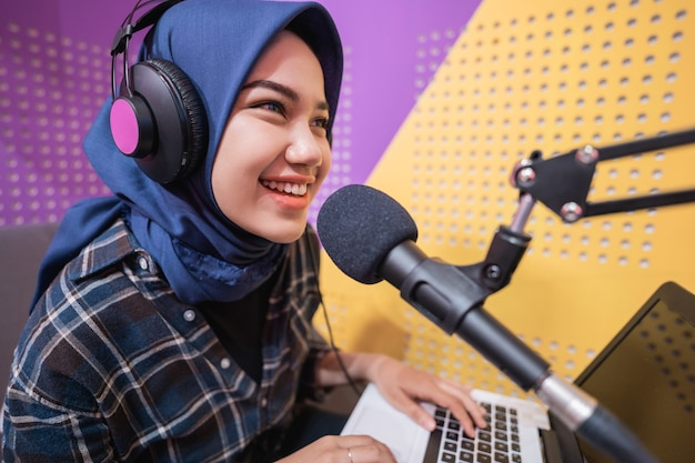 Aufgeregte muslimische frau nimmt einen podcast im studio mit laptop auf