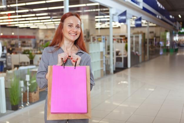 Aufgeregte reife frau, die einkaufstaschen hält, fröhlich lächelt, raum kopiert. glücklicher weiblicher kunde auf einkaufstour