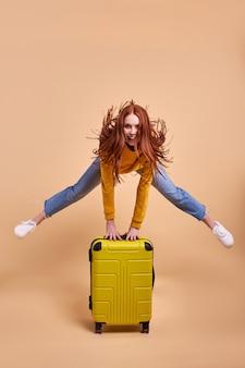 Aufgeregte reisende touristische rothaarige frau mit kofferspringen in lässigem outfit einzeln im studio kaukasische passagierin, die am wochenende ins ausland reist flugreisekonzept kopienraum