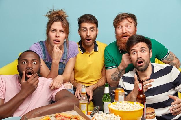 Aufgeregte schockierte gesellschaft von freunden sehen horrorfilm, starren mit verwanzten augen, halten das kinn, spielen videospiele, essen junk food, trinken bier, posieren auf der couch, isoliert über der blauen wand. freizeit und ruhe