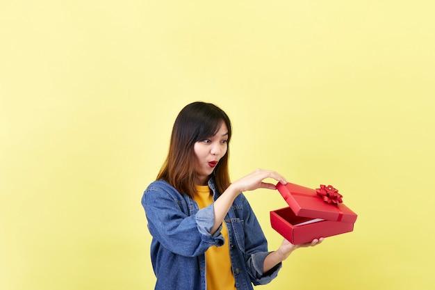 Aufgeregte schöne asiatische frau, die eine rote geschenkbox hält
