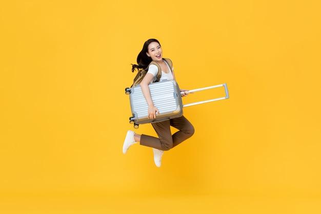 Aufgeregte schöne asiatische frauentouristin, die mit gepäck springt