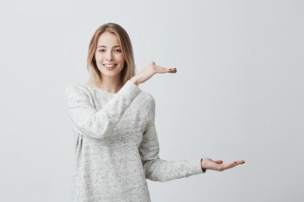 Aufgeregte schöne blonde frau in freizeitkleidung zeigt mit den händen länge der box. erfreute frau trägt einen losen pullover, lächelt freudig und zeigt die größe von etwas großem.