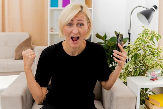 Aufgeregte schöne blonde russische frau sitzt auf sessel, der faust hält und telefon hält, das kamera im wohnzimmer betrachtet