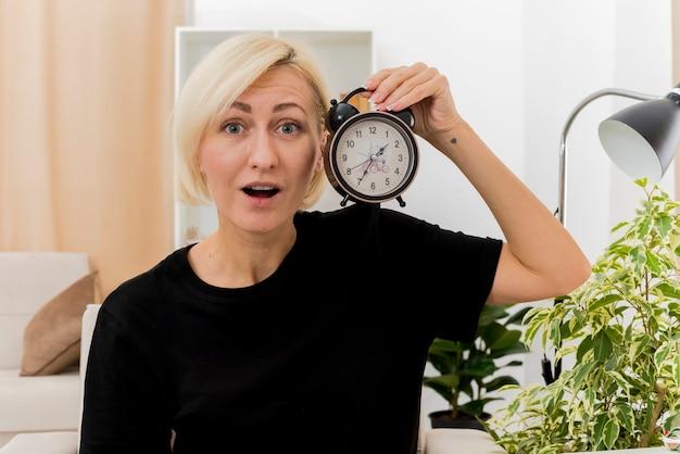 Aufgeregte schöne blonde russische frau sitzt auf sessel, der wecker nahe gesicht hält und kamera im wohnzimmer betrachtet
