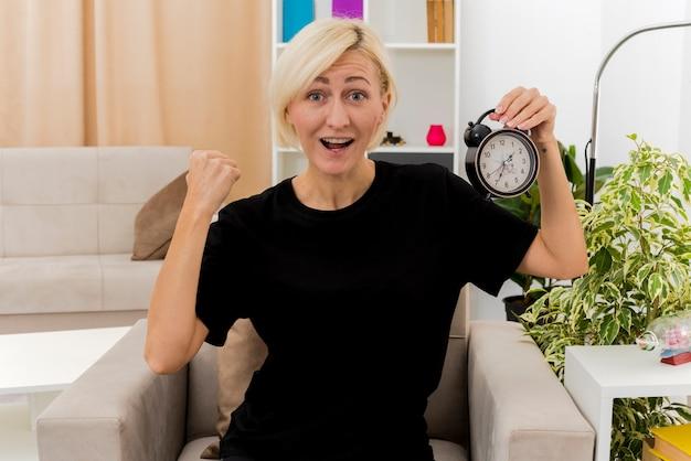 Aufgeregte schöne blonde russische frau sitzt auf sessel, hält faust und hält wecker im wohnzimmer