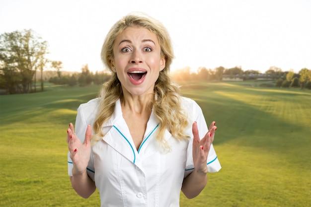 Aufgeregte schöne junge krankenschwester im freien. die glückliche junge krankenschwester oder ärztin hob ihre hände und öffnete den mund in großer aufregung über die natur.