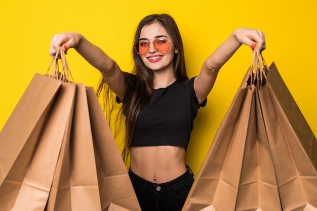 Aufgeregte schreiende junge frau, die isoliert über gelber wand steht, die einkaufstaschen und kreditkarte hält.