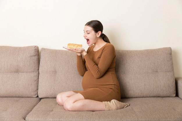 Aufgeregte schwangere frau isst ein stück kuchen