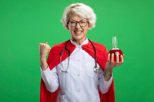 Aufgeregte slawische superheldenfrau in arztuniform mit rotem umhang und stethoskop in optischen gläsern hält faust und hält rote chemische flüssigkeit in glaskolben isoliert auf grüner wand mit kopierraum