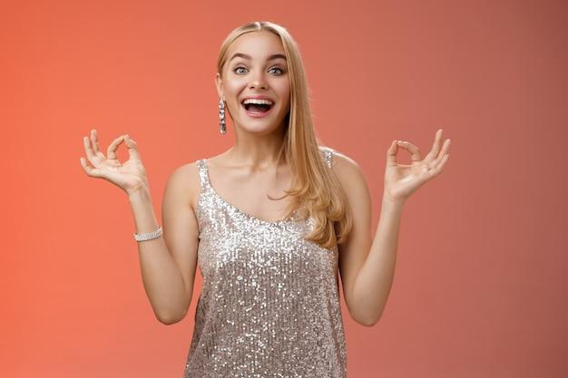 Aufgeregte sorglose glückliche stressfreie charmante blonde blonde europäische frau ruhige gefühle unter kontrolle zeigen zen-geste stehende nirvana lotus pose meditieren freudig lächelnd, beruhigt roten hintergrund.