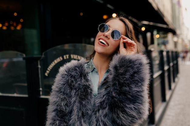 Aufgeregte stilvolle dame im trendigen outfit in der stadt. modeporträt hübsche frau im pelzmantel