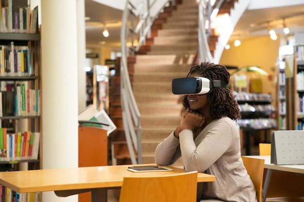 Aufgeregte studentin, die virtuelles video aufpasst