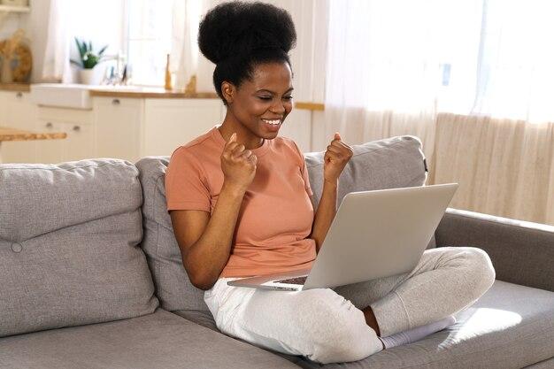 Aufgeregte tausendjährige afrikanische frau, die zu hause auf der couch sitzt, erhalten angenehme online-nachricht auf laptop