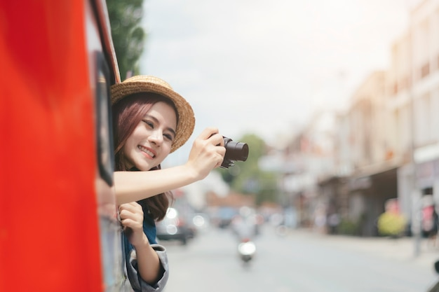 Aufgeregte touristen machen fotos, während sie auf dem auto sitzen.