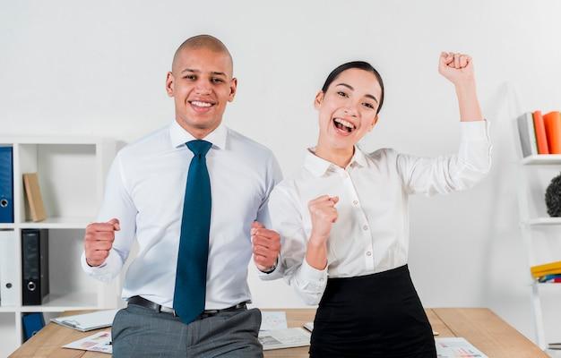 Aufgeregte überglückliche junge geschäftspaare, die vor tabelle am arbeitsplatz stehen