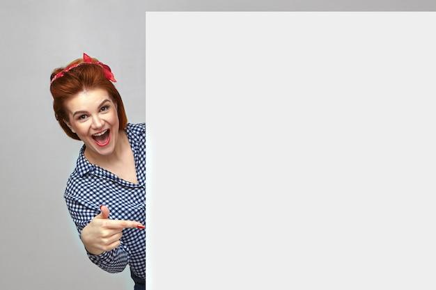 Aufgeregte, überglückliche junge hausfrau, die ein kariertes hemd und ein rotes stirnband trägt und den mund weit öffnet und ausruft