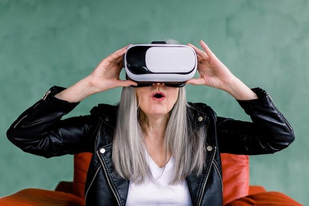 Aufgeregte, überraschte ältere dame mit glattem grauem haar, gekleidet in eine schwarze lederjacke, die auf einem roten stuhl sitzt und mit offenem mund durch eine brille schaut