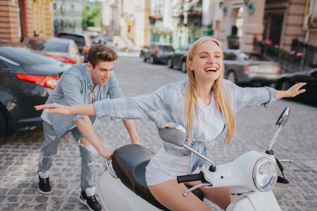 Aufgeregte und glückliche frau hält ihre hände beiseite des körpers in einer luft und hält ihre augen geschlossen weißer kerl steht hinter ihr und versucht, motorrad zu drücken