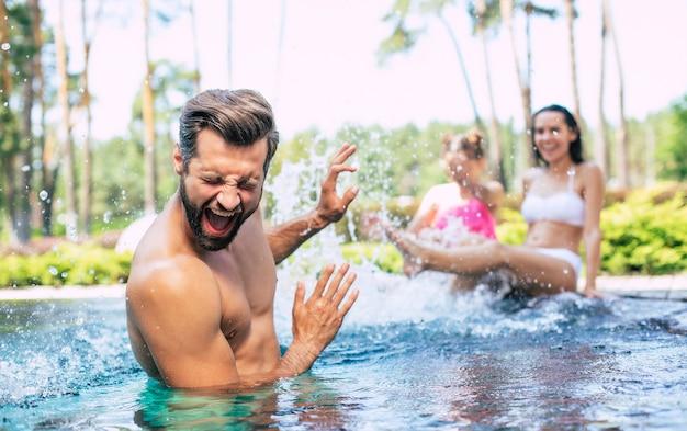 Aufgeregte und glückliche moderne schöne familie haben spaß im schwimmbad während der sommerferien.
