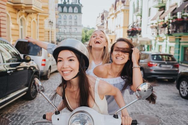 Aufgeregte und hinreißende freunde fahren auf einem motorrad.