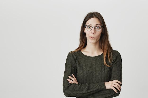 Aufgeregte und überraschte junge frau in brille hören faszinierende geschichte
