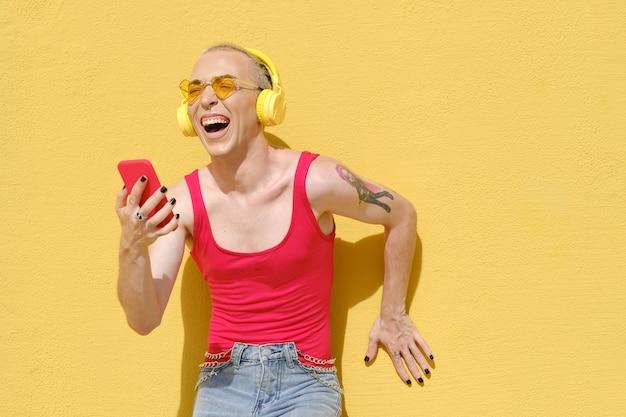 Aufgeregte und unbeschwerte nicht-binäre person, die lacht und spaß hat, während sie mit kopfhörern und einem mobiltelefon musik hört.