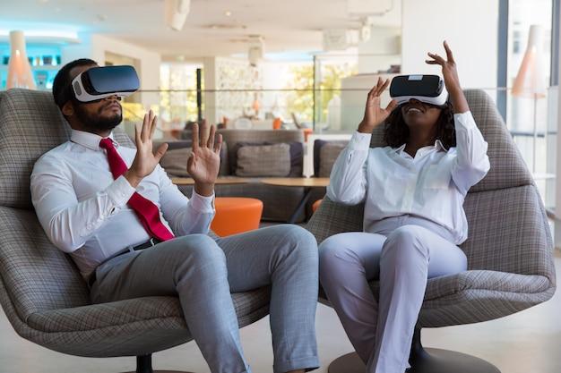 Aufgeregte verschiedene kollegen in vr-gläsern, die virtuelles spiel spielen