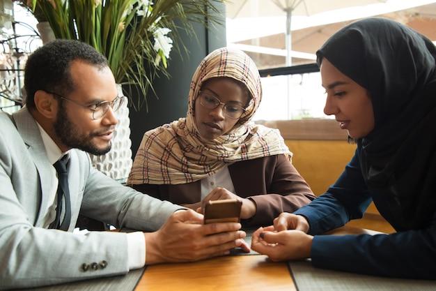 Aufgeregte verschiedene mitarbeiter, die inhalt auf smartphone aufpassen