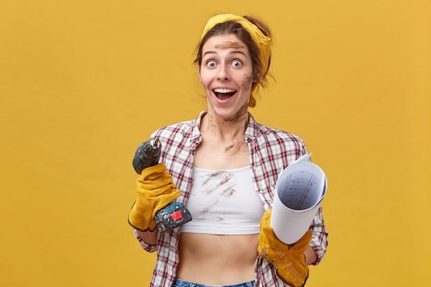 Aufgeregte weibliche arbeiterin, die mit abgehörten augen voller glück und geöffnetem mund schaut, während befördert wird, bohrmaschine und blaupause in ihren händen isoliert über gelber wand zu halten
