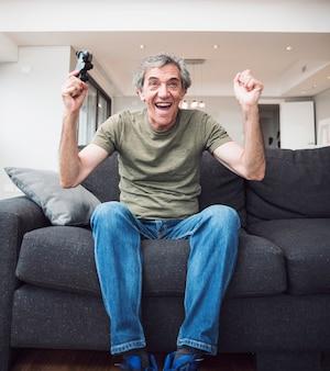 Aufgeregter älterer mann, der das videospiel gewinnt