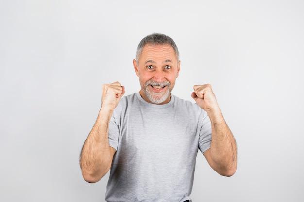 Aufgeregter älterer mann, der oben aufmuntert