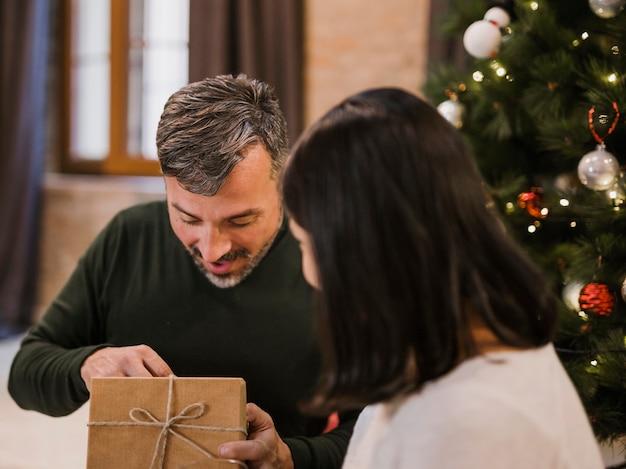 Aufgeregter älterer mann, der sein geschenk öffnet