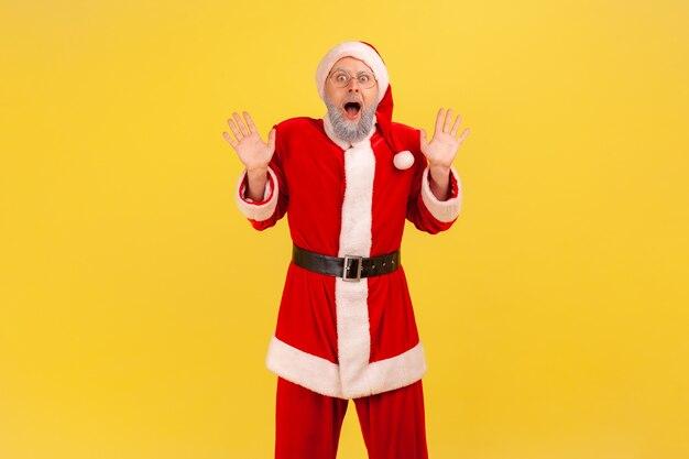 Aufgeregter älterer mann mit grauem bart im weihnachtsmann-kostüm, der mit großen augen und offenem mund in die kamera schaut, hat aktuelle nachrichten, erhobene arme. innenstudio erschossen auf gelbem hintergrund.