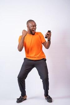 Aufgeregter afrikanischer mann feiert, während er auf sein telefon schaut und vor einem weißen hintergrund steht