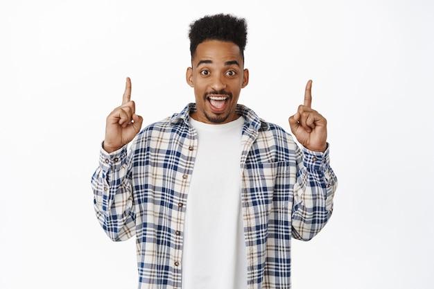 Aufgeregter afroamerikaner, der lacht, finger mit begeistertem, erstauntem gesichtsausdruck nach oben zeigt, rabattbanner zeigt, verkaufsankündigung unten auf weiß.