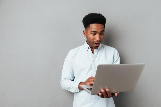 Aufgeregter afroamerikanischer mann, der laptop-computerbildschirm betrachtet
