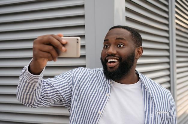 Aufgeregter afroamerikanischer mann, der selfie unter verwendung des mobiltelefons nimmt, das auf städtischer straße steht. emotional blogger influencer shooting video